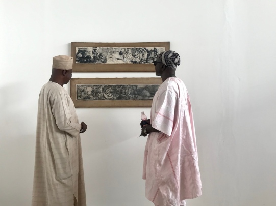 """Visitors to 'In Pursuit of something """"Beautiful"""",...perhaps' with Dawson's """"Kwasia Dwaso"""" and """"Iron Traditional Smith"""" (1995). Image Image courtesy of the artist and SCCA."""